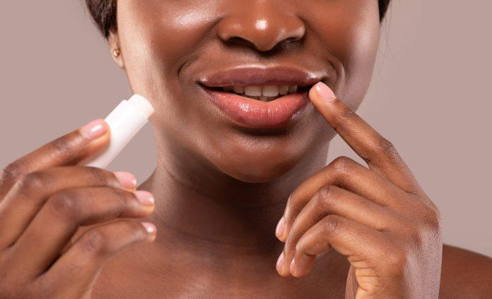 Black woman treating lip discoloration