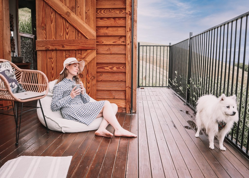 Women drinking coffee on the deck of Te Tuhi Hut with her dog