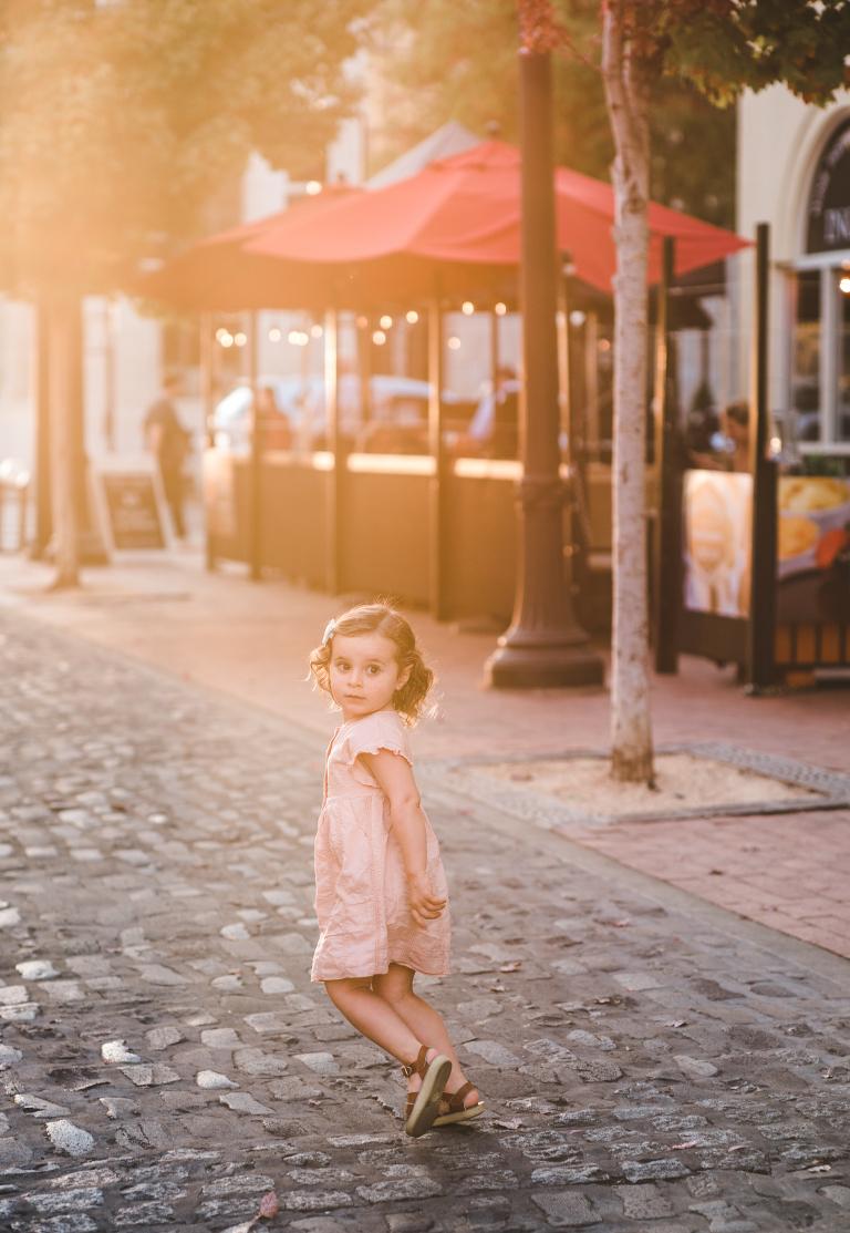 downtown Petaluma, cobblestone street, brick sidewalk, little girl, Saltwater sandals, peach dress, curly hair