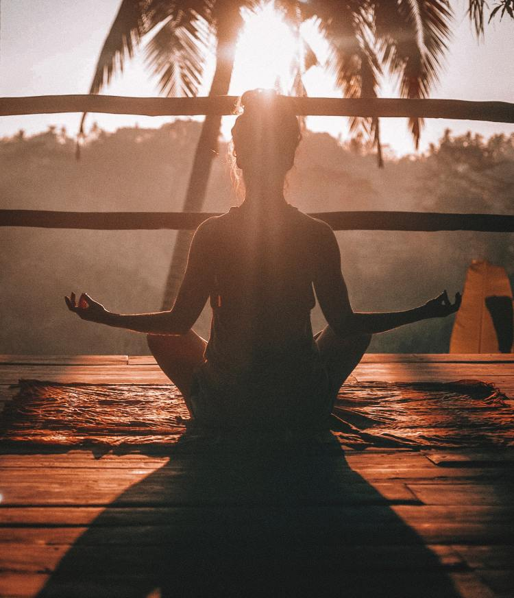 Backlit woman doing mindfulness meditation while sitting on a deck and facing palm trees and a sunset. The image evokes calm in the face of anxiety, which the accompanying essay by Emily P.G. Erickson addresses.