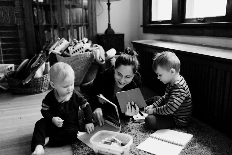 Photo by Jessica Holleque of Emily P.G. Erickson speaking and explaining things about mental health, culture, mindfulness, and motherhood to her children.
