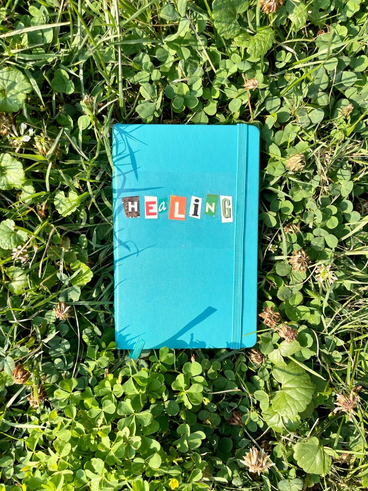"""Journal with collaged cover that reads, """"healing"""" by Emily P.G. Erickson"""