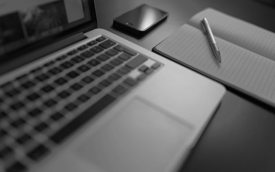 black and white photo of a laptop keyboard and notebook