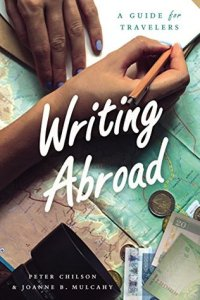 Writing Abroad cover featuring a hand writing in a notebook over maps