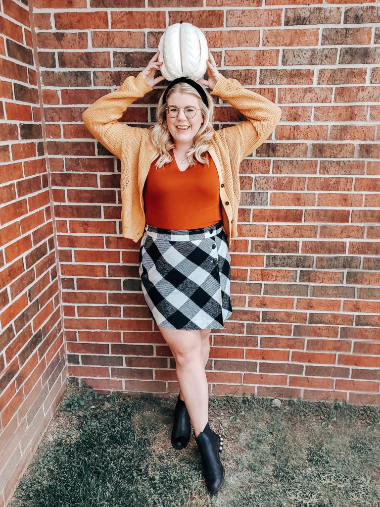 Emily in a thrifted fall styles cardigan, tshirt, plaid skirt, and ankle booties
