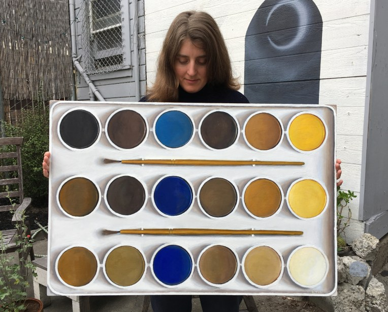 Me with my painting Portrait of a Color Blind Artist's Watercolor Tray — Red-Green Color Blind Simulation, 2016, oil on wood panel, 24 x 36 inches. This is what Brian's new watercolor palette looked like to him when he first handed it to me to be labeled. Photo by Brian Brooks