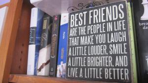 """A bunch of books and a black sign that says """"Best Friends are the people in life that make you laugh a little louder, smile a little better and live a little better."""