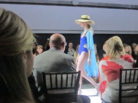 """A blonde woman wearing a beige floppy hat, dark blue one piece suit and light blue cape at Unbound. Part of Maxine Archambault's """"Ocean Breeze"""" collection"""