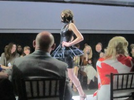 A brunette woman wearing a black dress with a cage like skirt designed by Nidia Martinez at Unbound 2-16