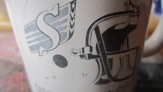 A white mug with the Saskatchewan Roughriders logo on it