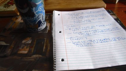 A white sheet covered in blue writing in a notebook with a gengar glass