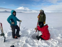 Meghan and Matt watching Chloe test if the kovaks drill works for installing a magnetometer sensor during our deep field shake down test. Mount Erebus is in the background.