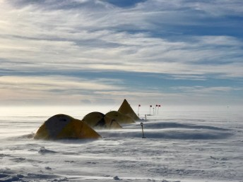Sleeping tents with drifting snow.