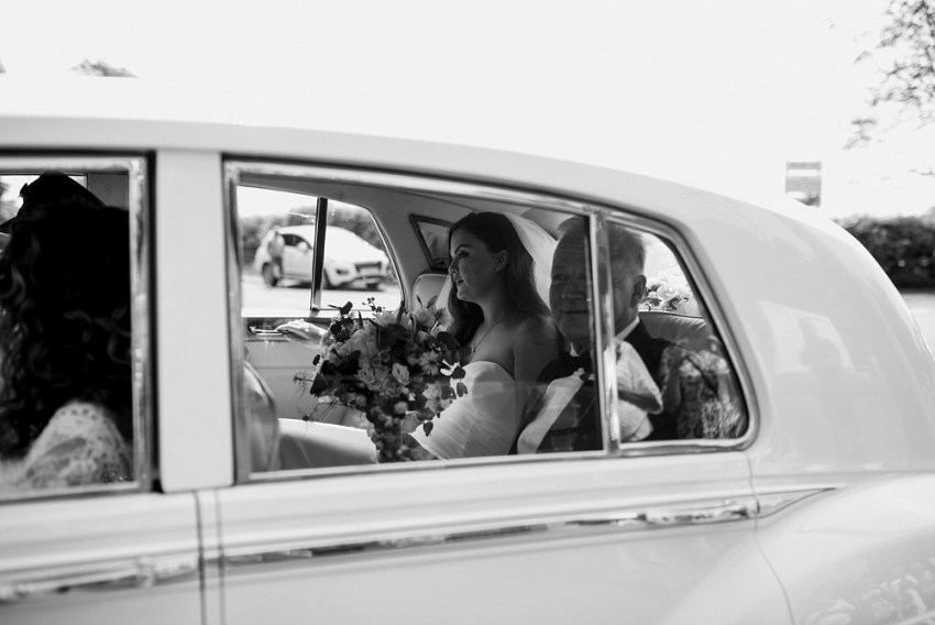 bride and her dad arrive at church in wedding car