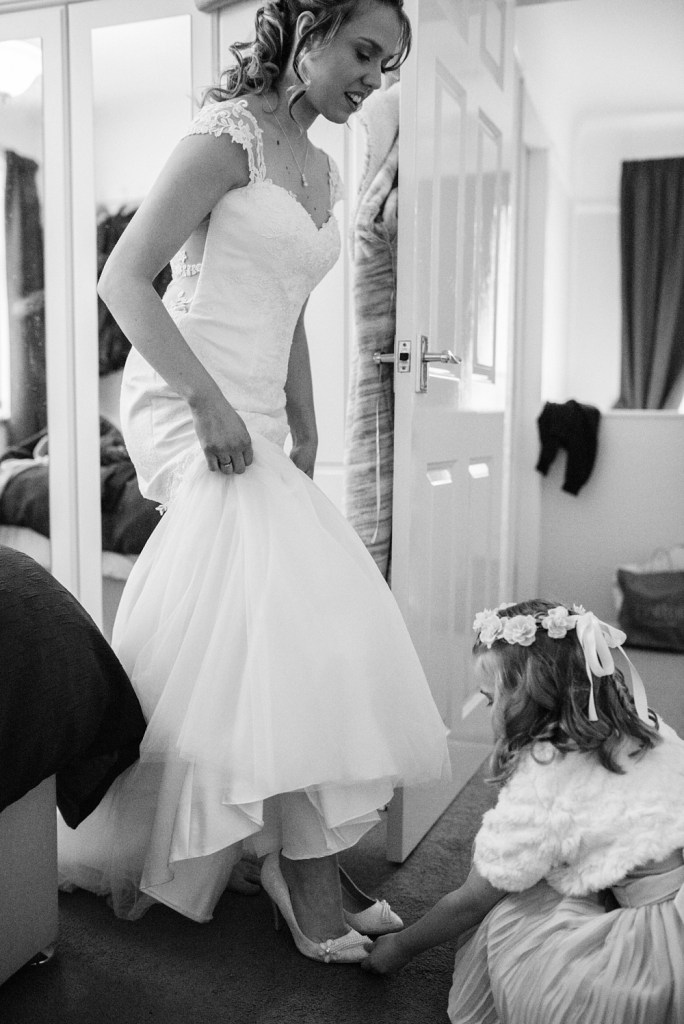flower girl helping bride with shoes