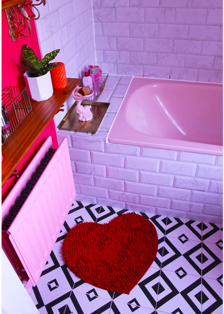 pink bathroom with pink bathtub and red heart bathmat