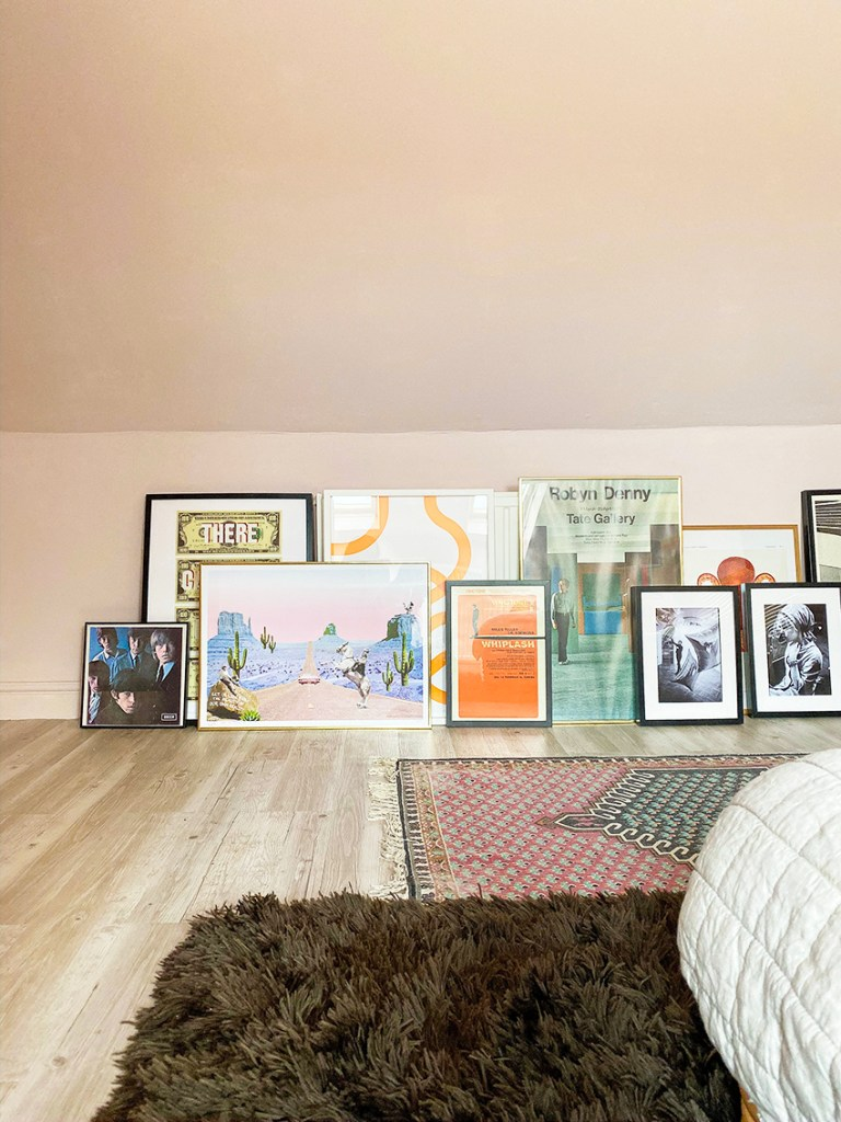 pink 70s bedroom with leaning artwork and brown shaggy rug