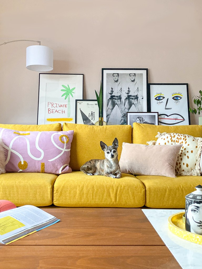 peach living room with mustard John Lewis sofa and mauve cushions and framed artwork