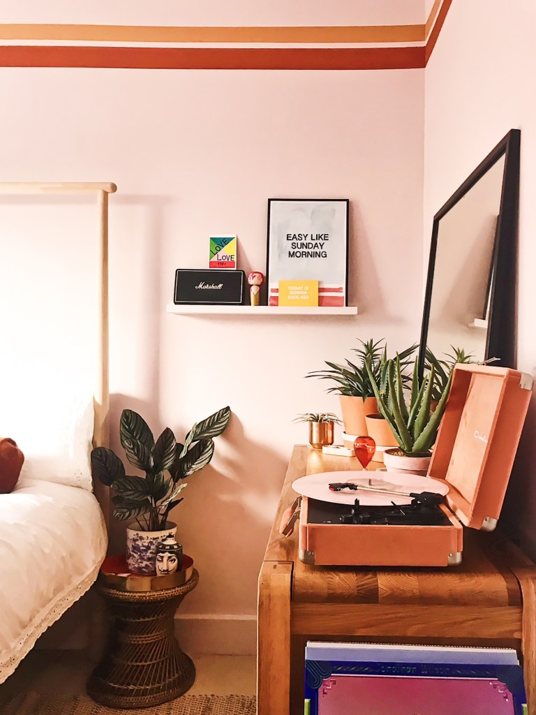 art on picture shelf in pink retro bedroom