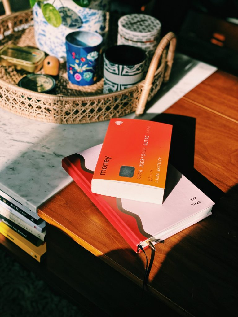 orange guide to money book on coffee table.
