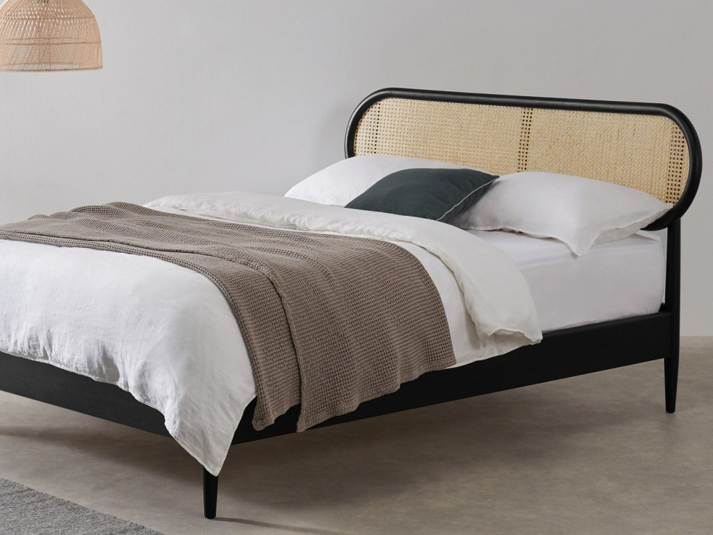 Black bed with rounded cane headboard