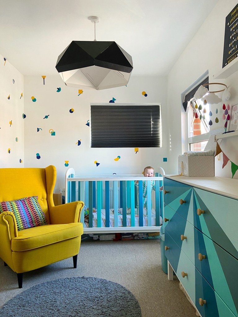 colourful nursery with blue cot and yellow chair