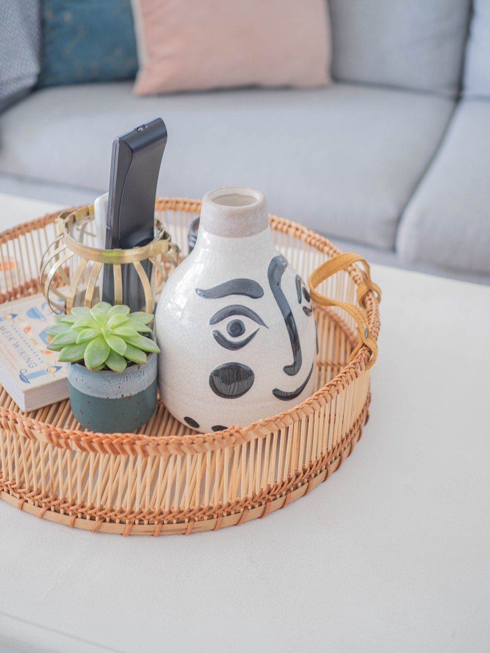 wicker tray on coffee table with abstract vase