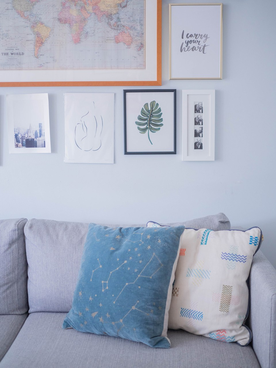 grey sofa with blue cushions and gallery wall
