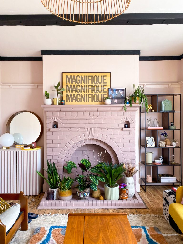 pink fireplace with plants and yellow artwork