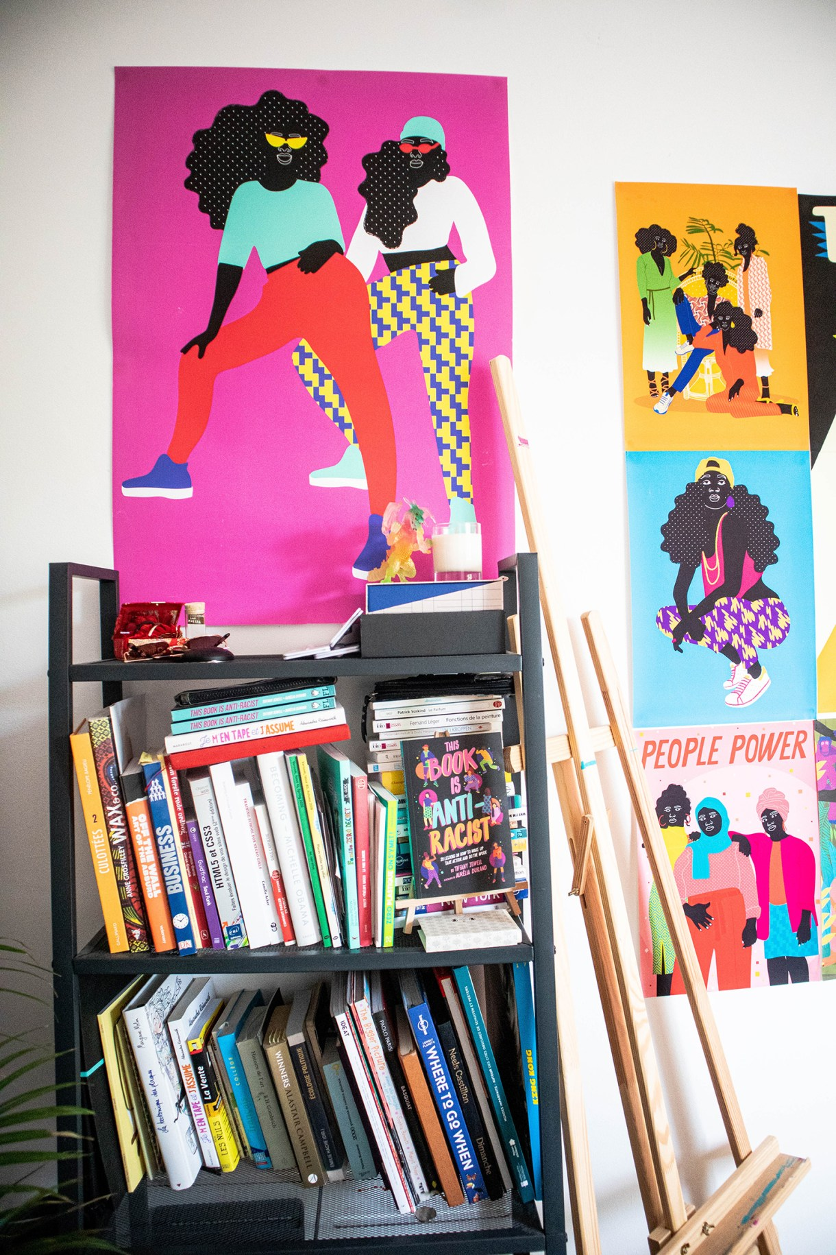 bookshelf with colourful prints on the wall