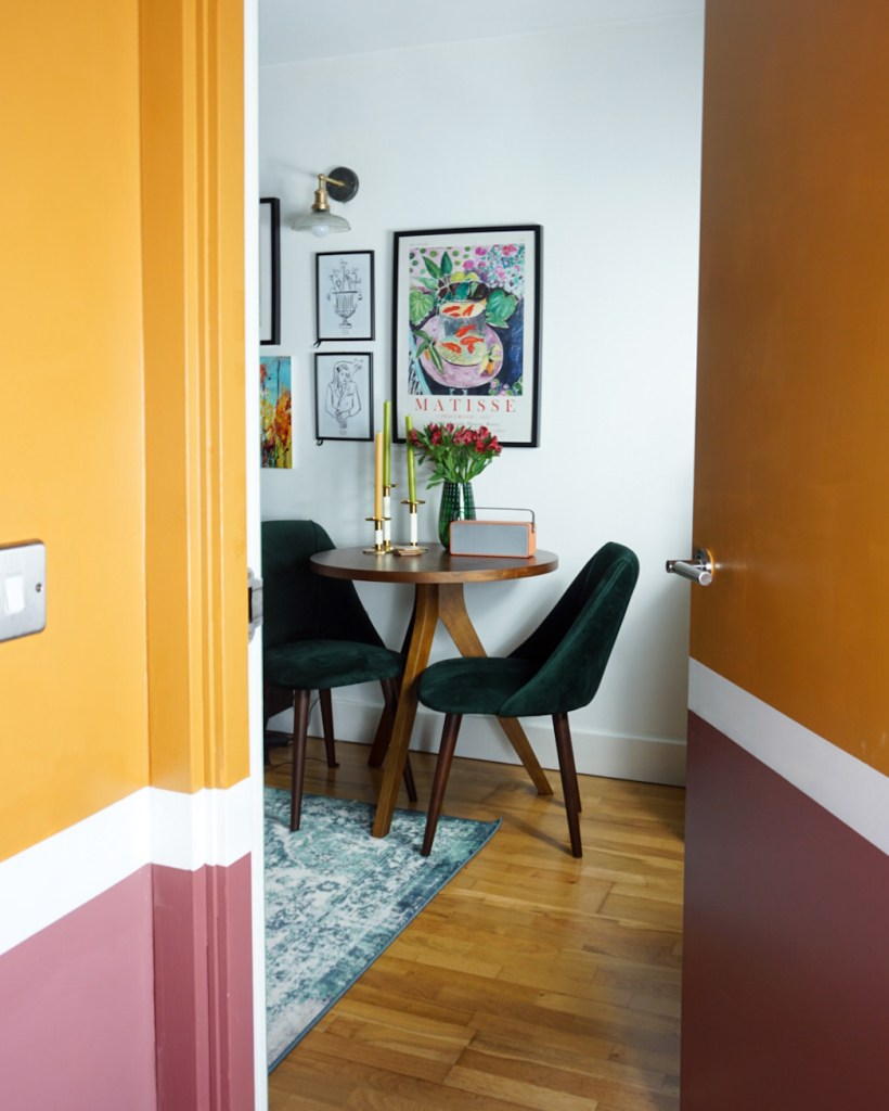 white dining room leading into pink and yellow hallway