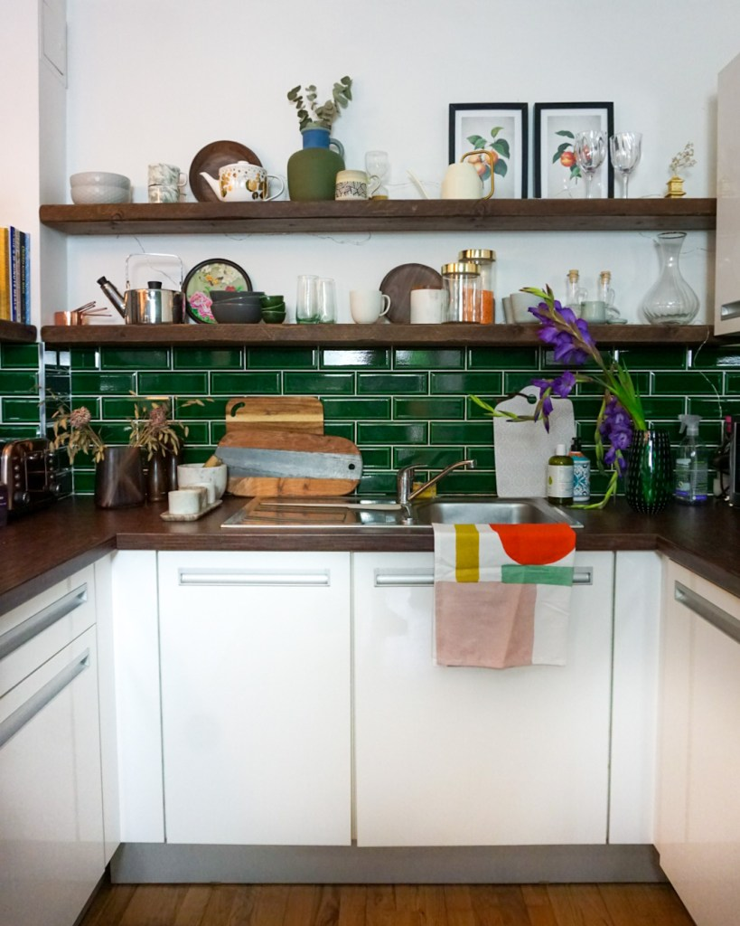 white kitchen with emerald green tiles