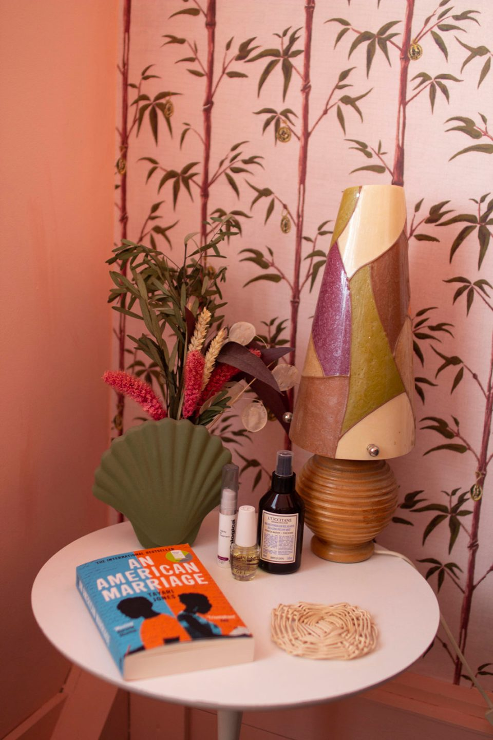 coral pink and bamboo wallpaper behind bedside table with vintage lamp