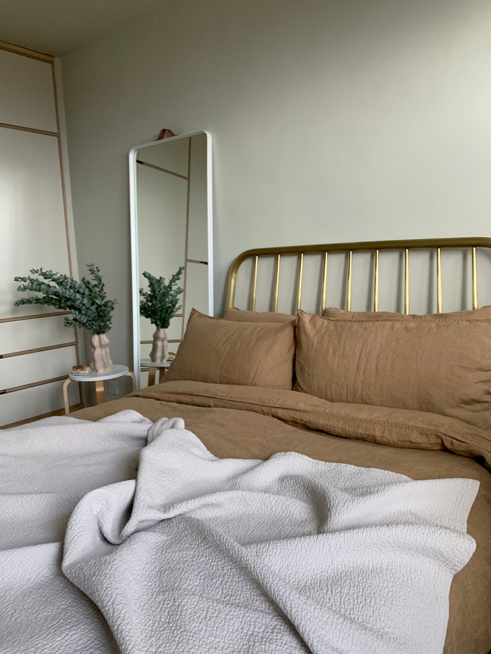 neutral bedroom with gold be frame and tan bed linene