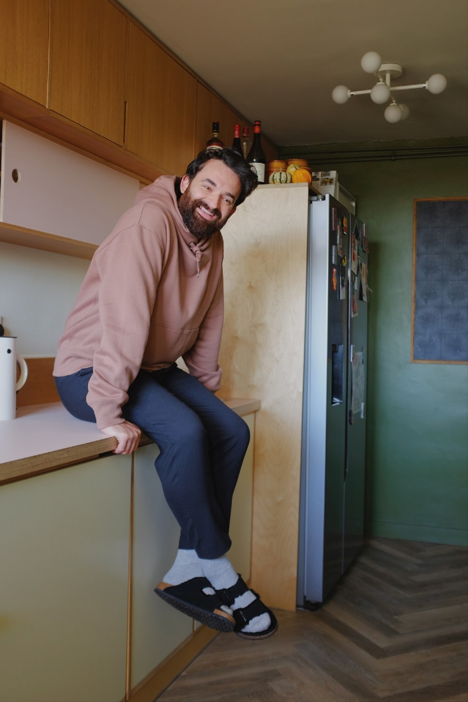 james in pink hoodie and jeans on kitchen countertop