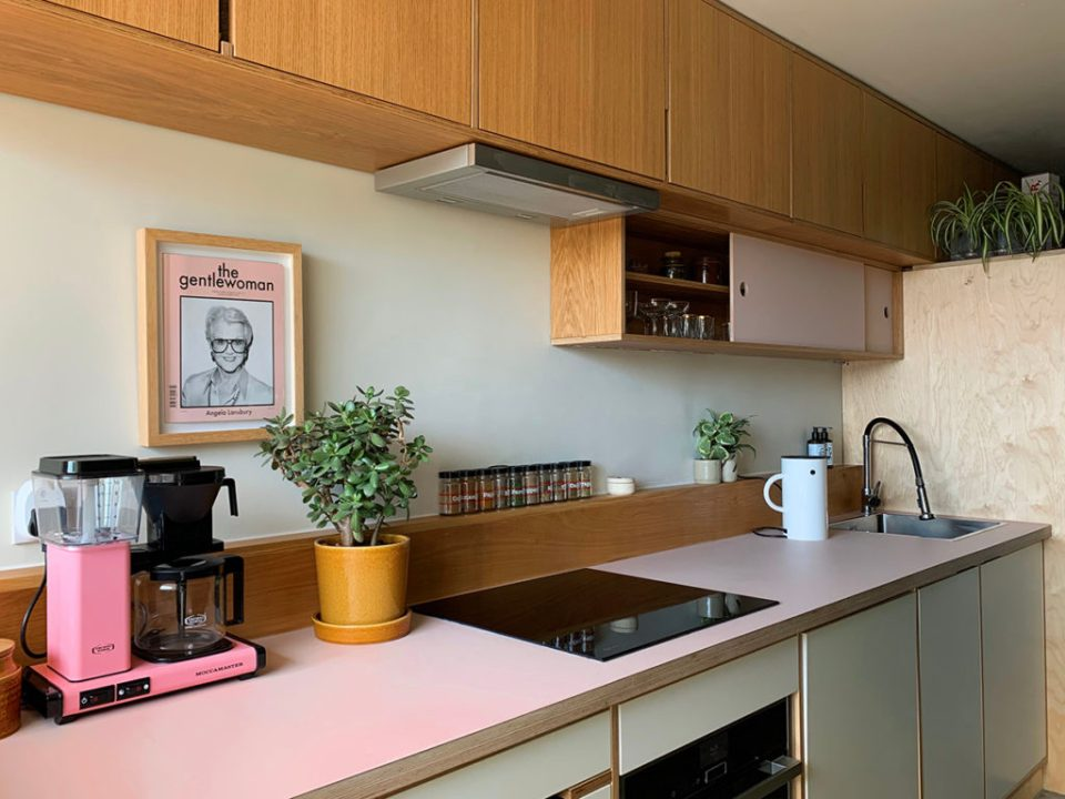 mint and pink kitchen with olive green wall and wooden cabinets
