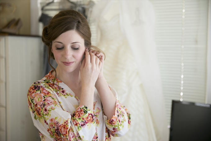 bride putting on earrings in this Crystal Coast Wedding | North Carolina wedding photographed by Ellen LeRoy Photography - http://emmalinebride.com/real-weddings/breathtaking-crystal-coast-wedding-mara-will-married/