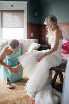 The Bride and Her Bridesmaid Helping Her Get Ready - Bald Head Island Wedding - Photo by Eric Boneske