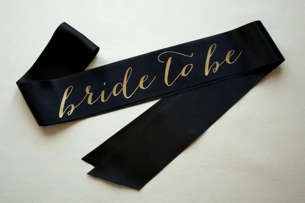 black bride to be sash with gold | stylish bachelorette sash ideas | via http://emmalinebride.com/bride/bachelorette-sash-ideas/