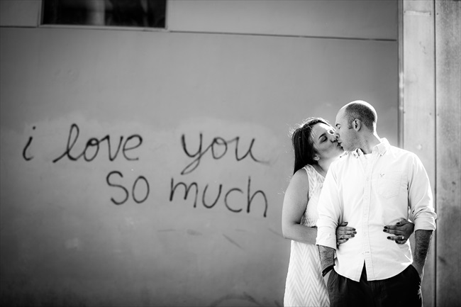 engaged couple kiss by graffiti that says,