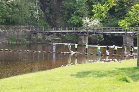 Kids crossing the stepping stones at Bolton Abbey