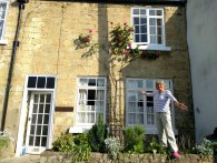 Ann showing off the roses outside her cottage