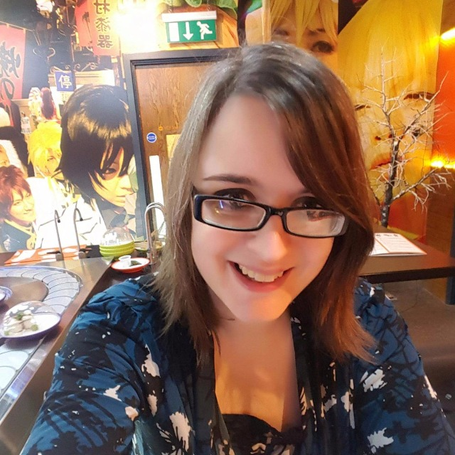 Selfie of Emma in a bright, colourful sushi restaurant with Japanese manga-style art on the walls