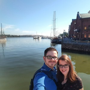 Emma and Dave in Helsinki, standing at a harbour. The water is flat, clear and blue and there are many boats in the background.
