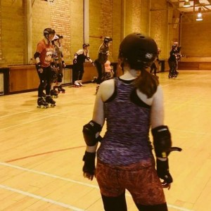 Emma in gym gear at her first roller derby match. Here's an alt-text secret: I'm actually sitting on my knees in this photo. I spent a LOT of time kneeling while figuring it all out.