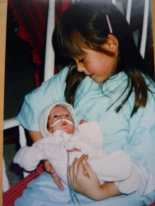 that's tiny me with my older sister and best friend in the whole world. she saves tiny babies for a living.