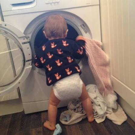 toddler pulling clothes out of washing machine inside the house