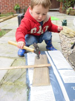child hammering a sign in the garden