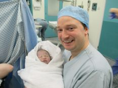 man and new born baby after c-section