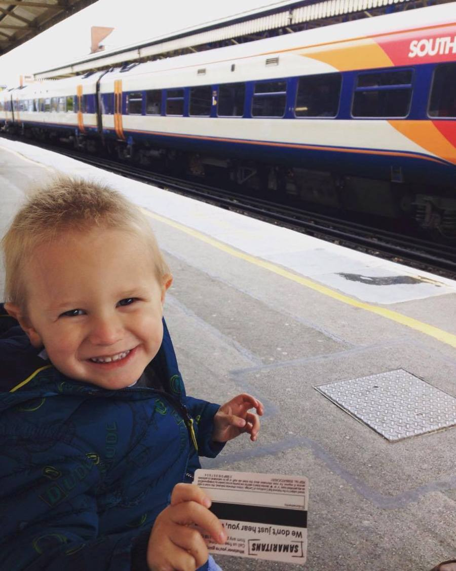 Jake holding a rail card with a train in the background